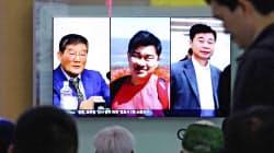北朝鮮に拘束されていた米国人3人の画像を映すテレビに見入るソウル市民ら=AP