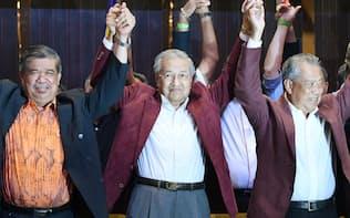 記者会見で手を取り合って喜ぶマハティール元マレーシア首相(中)(10日未明、クアラルンプール郊外)=柏原敬樹撮影
