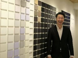 森雄一郎社長。銀座7丁目店の壁面には布地のサンプルが並ぶ。