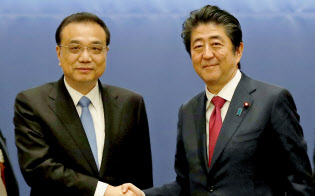 日中知事省長フォーラムで握手する中国の李克強首相(左)と安倍首相(11日午前、札幌市内のホテル)=共同