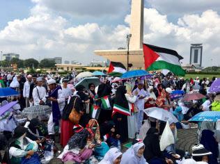 11日、ジャカルタの独立記念塔の前でパレスチナの旗を掲げるデモ参加者たち