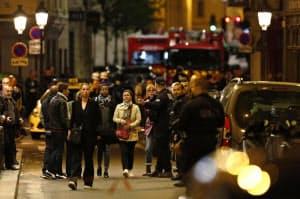 警官に誘導され、刃物で通行人が襲撃された現場周辺から避難する住民(12日、パリ)=AP