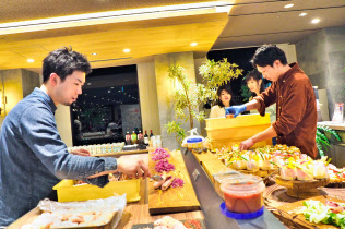 出張先で料理を盛りつけるシェフの徳田さん