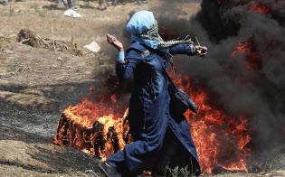 14日、パレスチナ自治区ガザのイスラエル境界付近のデモでイスラエル軍に向かって石を投げるパレスチナ人女性=AP