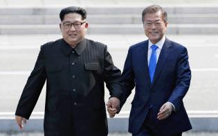 南北首脳会談で韓国の文在寅(ムン・ジェイン)大統領(右)と軍事境界線を越える北朝鮮の金正恩(キム・ジョンウン)委員長(4月27日、板門店)=韓国共同写真記者団・共同