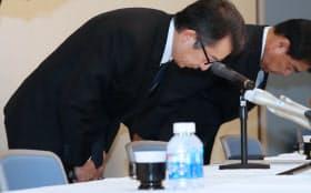 記者会見で頭を下げるスルガ銀行の米山明広社長(左)=15日午後、静岡県沼津市