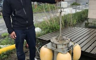 水温や塩分濃度を測定するブイを手にするノリ漁師の津田さん