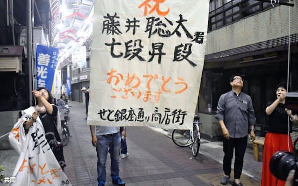 藤井聡太七段の誕生を祝い、垂れ幕を掲げる地元のファンら(18日午後9時ごろ、愛知県瀬戸市)=共同