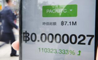 個人投資家のスマホ画面に表示された、仮想通貨の上昇率11万%を示す数字(下)