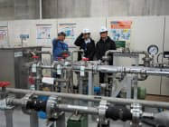 泊原発の訓練用設備について説明を受ける更田委員長(右)(19日、北海道泊村)