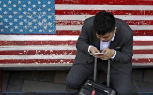中国はネット検閲の人手が足りなくなっている(北京のベンチで携帯電話を操作する人)=AP