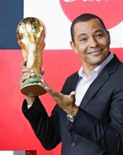 W杯優勝トロフィーを手にするのはどこか。4年に1度の大舞台がまもなく幕を開ける(トロフィーを披露する元ブラジル代表のジウベルトシウバ氏)=共同