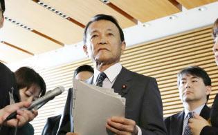閣議後会見で質問に答える麻生太郎財務相(中央)(25日午前、首相官邸)=時事