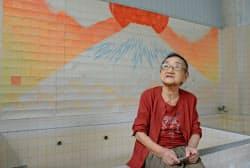 チョン・ホイ・イさん(マカオ)の木版画「高砂湯の富士さん」を背に銭湯の思い出を語る福岡二三子さん(26日、甲府市)