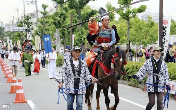 南北朝時代を再現したよろいかぶとや着物姿で市街地を練り歩く「楠公武者行列」(26日、神戸市)=共同