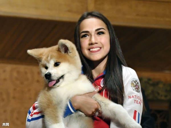 贈呈された秋田犬の子犬を抱くアリーナ・ザギトワ選手(26日、モスクワ)=共同
