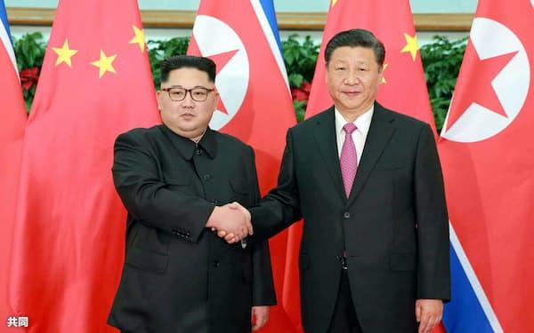 北朝鮮の労働新聞が9日掲載した、中国・大連で握手する金正恩委員長(左)と習近平国家主席の写真(コリアメディア提供・共同)