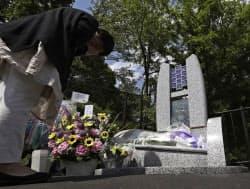 事故現場付近に設置された「祈りの碑」に手を合わせる女性(27日午後、長野県軽井沢町)=代表撮影・共同