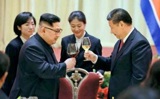 北朝鮮の労働新聞が9日掲載した、中国遼寧省大連で乾杯する金正恩朝鮮労働党委員長(左)と習近平国家主席の写真=コリアメディア提供・共同