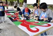 6月に開幕するサッカーW杯に向けたイベントで、ヨルダンののぼりを作る市民ら(28日、福岡県太宰府市)=共同