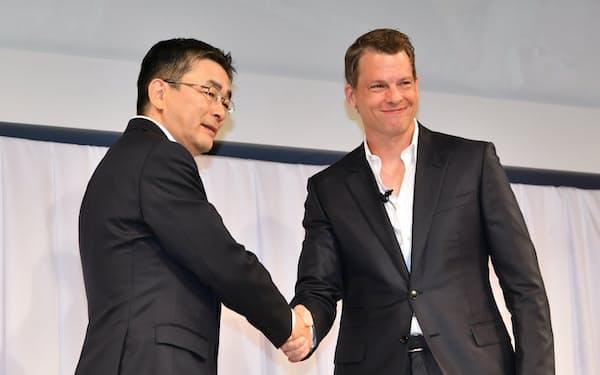 業務提携を発表し握手するKDDIの高橋誠社長(左)とネットフリックスのプロダクト最高責任者のグレッグ・ピーターズ氏(29日午前、東京都新宿区)