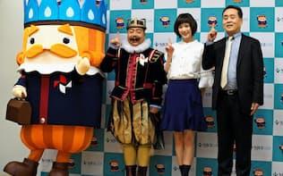 CM出演者らと写真に収まる日ガスの和田真治社長(右)