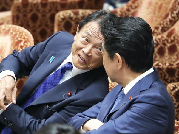 衆院予算委で安倍首相(右)と言葉を交わす麻生財務相(28日)