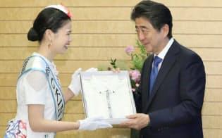 ミス沖縄の末吉古都子さん(左)からかりゆしウエアを贈られる安倍首相(31日午前、首相官邸)