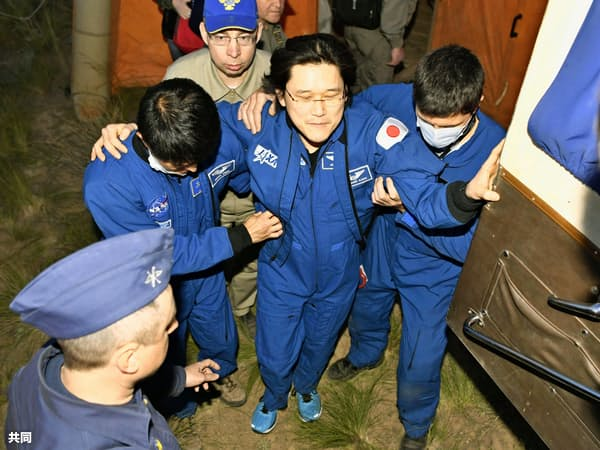 地球に帰還後、肩を支えられながら歩く金井宣茂さん(中央)(3日、カザフスタン)=共同