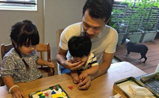 自宅での仕事の合間に子供と遊ぶ松本さん