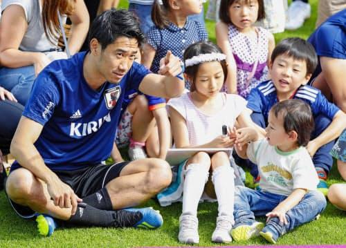 ゼーフェルトの練習場を訪れた子どもたちと穏やかな表情で話す香川(手前左)=共同