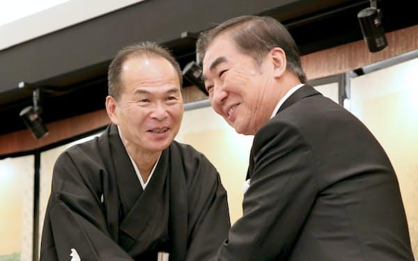 記者会見で握手する新会長の笑福亭仁智(左)と前会長の桂文枝(5月31日、大阪市北区)