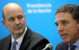 7日、IMFとの合意を発表するアルゼンチンのドゥホブネ財務相(右)(ブエノスアイレス)=ロイター
