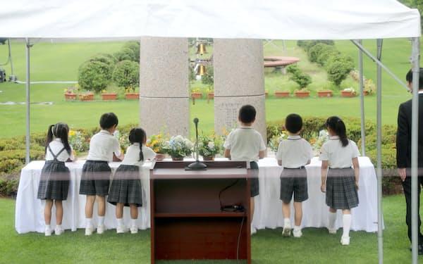「祈りと誓いの塔」に献花する児童(8日午前、大阪府池田市の大阪教育大付属池田小)
