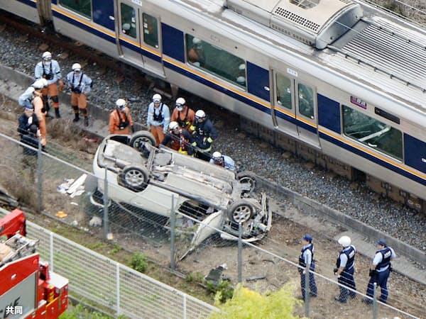 JR片町線の線路内で電車と衝突し横転した乗用車(9日午前、大阪府大東市)=共同
