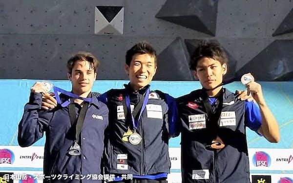 W杯ボルダリング第6戦の男子で優勝し、表彰式で喜ぶ杉本怜(中央)と3位の楢崎智亜=右(9日、ベイル)=日本山岳・スポーツクライミング協会提供・共同
