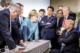 対峙するメルケル独首相とトランプ米大統領。その奥で腕組みする安倍首相=ロイター
