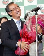 新潟県知事選で当選を決め、花束を手に笑顔の花角英世氏(10日夜、新潟市中央区)=共同