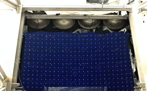 スーパーカミオカンデ改造。12年ぶりにふたを開けたスーパーカミオカンデのタンク。ゴムボートが浮かび、水底に光センサー群が粒状に見える。水面には天井が映り込んでいる。6月10日撮影
