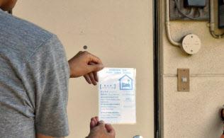 新法で掲示が必要となったステッカーを貼る家主(東京都内)=一部画像処理をしています