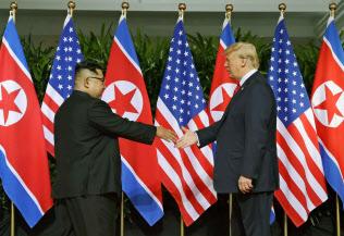 会談の冒頭で握手を交わす北朝鮮の金正恩朝鮮労働党委員長(左)とトランプ米大統領=12日、シンガポール(AP=共同)