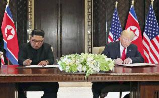 合意文書に署名する北朝鮮の金正恩委員長(左)とトランプ米大統領(12日、シンガポール)=ロイター