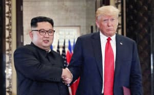 合意文書を交換し、握手する北朝鮮の金正恩委員長(左)とトランプ米大統領(12日、シンガポール)=ロイター