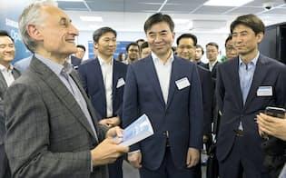 サムスンはAI分野で英ケンブリッジ大教授(左)ら欧米の権威と関係を深める(5月22日、英国のAI研究センター開設式)   と談笑するサムスン幹部ら(5月22日、英ケンブリッジ)
