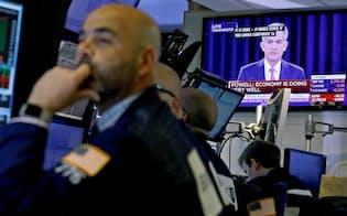 13日、ニューヨーク証券取引所のテレビに映るパウエルFRB議長の会見=ロイター