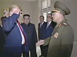 12日の米朝首脳会談で努光鉄・人民武力相に敬礼するトランプ米大統領(左)(シンガポール)=AP