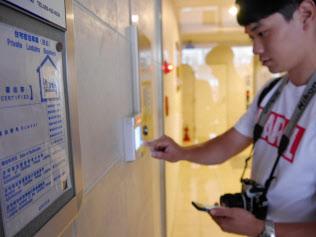 スマホに送られた解錠キーで民泊用の物件に入る訪日外国人(15日、福岡市)