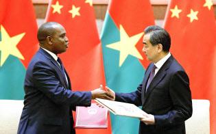 中国は5月、ブルキナファソと国交を結んだ(北京の釣魚台迎賓館で行われた署名式で握手するブルキナファソのバリー外相(左)と中国の王毅国務委員兼外相)=共同