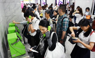 携帯電話がつながりにくくなり、公衆電話に並ぶ人たち(18日午前、大阪市北区のJR大阪駅)=目良友樹撮影