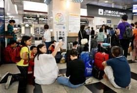 JR大阪駅で運転再開を待つ訪日外国人(18日午後、大阪市北区)
